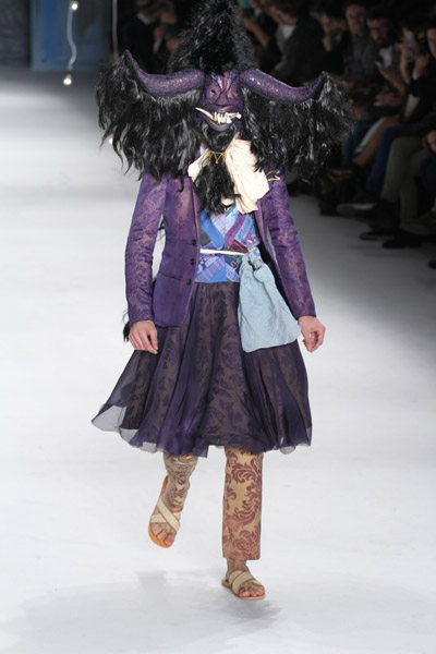 """João Pimenta abriu seu desfile de Verão 2013 com um modelo usando conjunto de calça, saia e blazer estampados com flores e """"fantasiado"""" com uma máscara de folclore"""