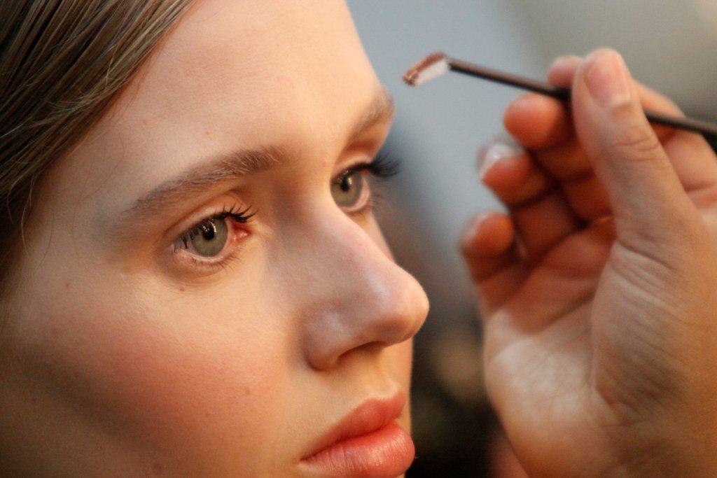 Modelo recebe retoques finais na maquiagem para desfile de Reinaldo Lourenço na SPFW