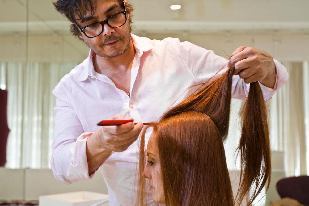 Depois de lavar e dar uma leve escovada no cabelo, aplique uma mousse ou gel para estruturar os fios. Separe uma linha central na largura de dois dedos até o osso atrás da cabeça (veja acima)