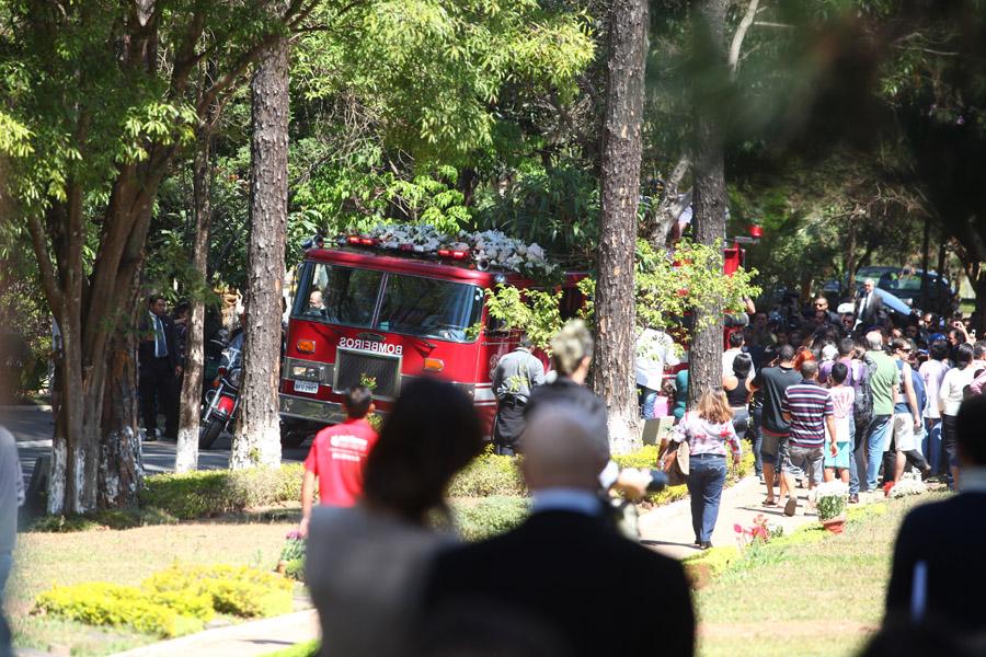 Carro do Corpo de Bombeiros entra no Cemitério Gethsemani, no bairro do Morumbi, trazendo o caixão de Hebe Camargo, que foi coberto pela bandeira do Brasil. Fãs e admiradores da apresentadora a receberam com aplausos