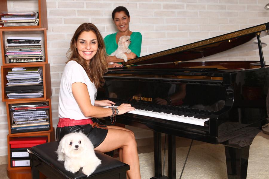 Em sua casa, em São Paulo, a cantora Aline Muniz toca piano sob o olhar atento da mãe, Angelina
