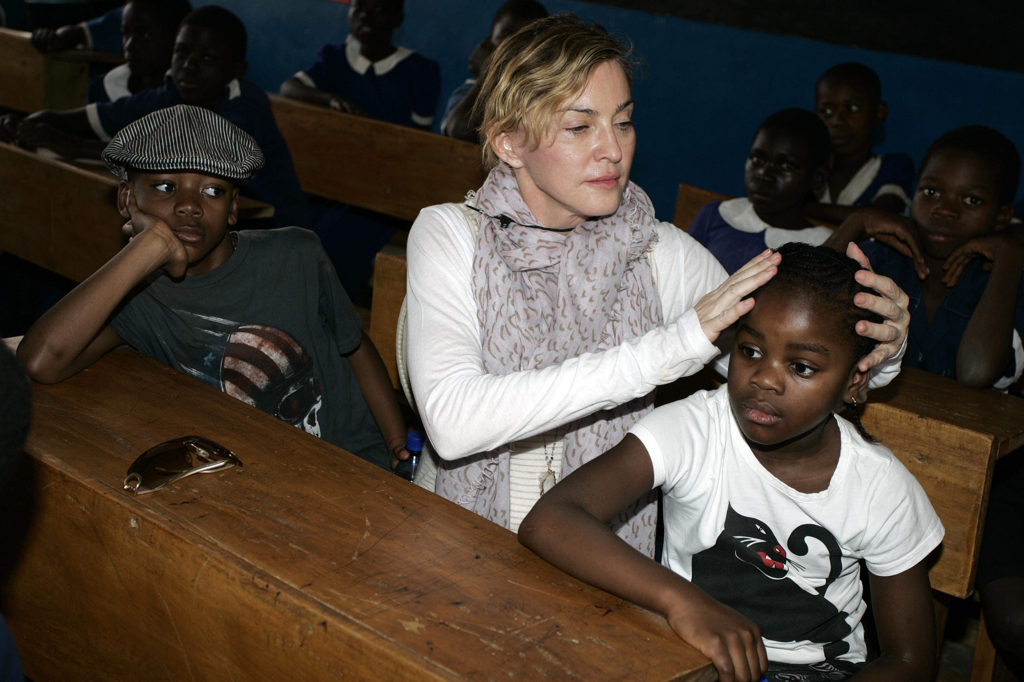 Madonna com David Banda e Mercy James no Malauí - filhos que ela adotou no país. A cantora ainda é mãe biológica de Lourdes Maria e de Rocco.