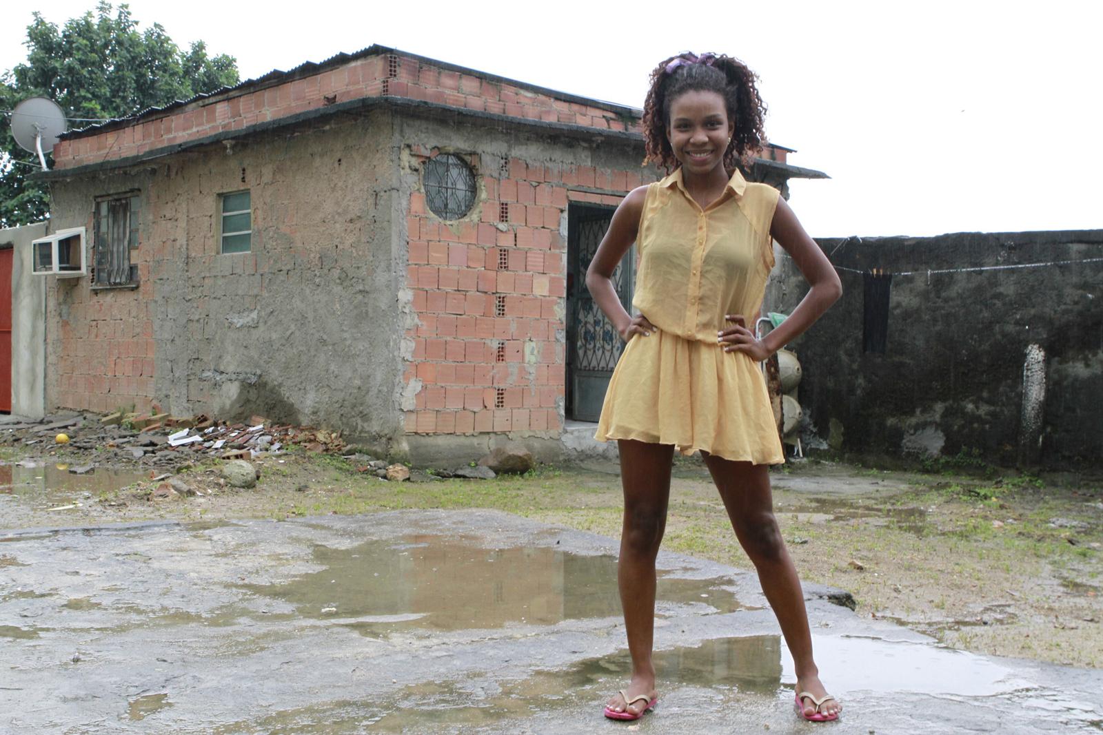 Luane Dias na frente de sua casa, nos fundos de um conjunto habitacional na Zona Norte do Rio.