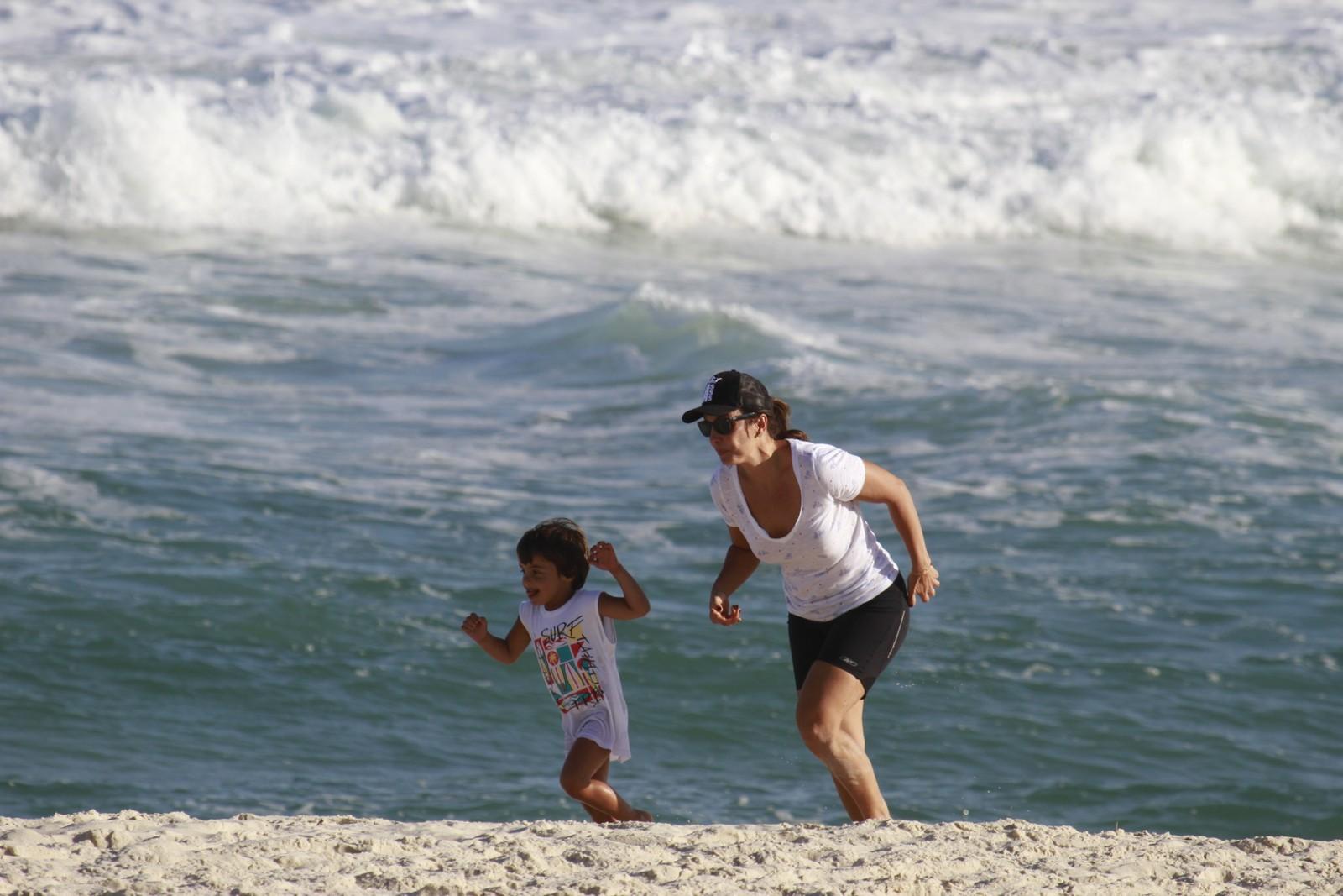 Ivete Sangalo corre com o filho na praia.