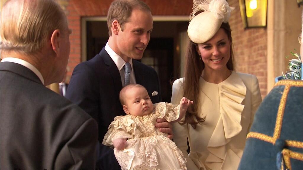 Príncipe William sorri com o herdeiro no colo, ao lado de Kate Middleton. O casal levou o pequeno para ser batizado nesta quarta-feira, 23
