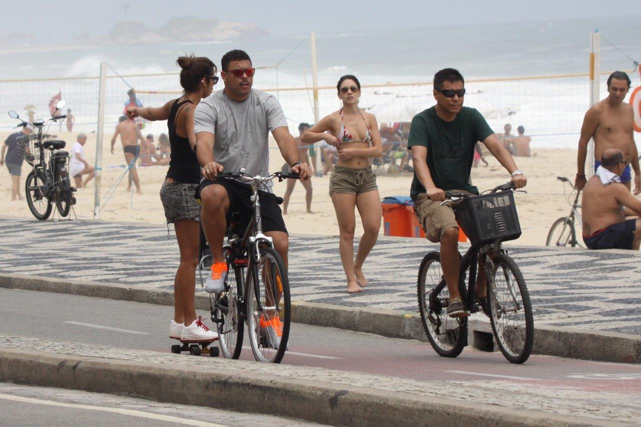 Ronaldo anda de bicicleta e Paula Morais vai de skate, segurando na garupa, neste domingo, 8, na orla do Leblon, Zona Sul do Rio