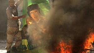 24 de agosto - Rebelde queima pôster de Muammar Kadhafi em Bab al-Aziziya (Foto: AFP)