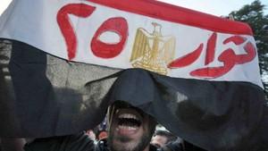 Manifestante egípcio segura bandeira onde se lê 'Manifestantes do 25º' em referência ao dia 25 de fevereiro, data da queda do ex-ditador Hosni Mubarak (Foto: Mohamed Hossam/AFP)