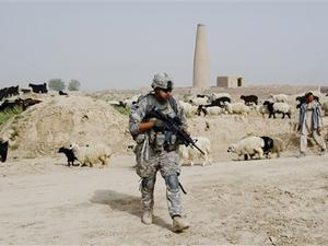 Soldado americano passa por pastor afegão durante patrulha na província de Kandahar nesta quarta-feira (21). (Foto: AP)