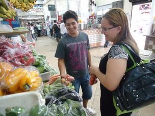O comerciante Antônio Utyama atende Carolina Abreu, que gosta de consumir tomates nas refeições (Foto: Adriane Souza/G1)