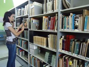 A bibliotecária Flávia diante de parte do acervo da biblioteca municipal (Foto: Adriane Souza/G1)