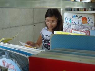 Júlia tenta escolher os próximos livros na área infantil da biblioteca (Foto: Adriane Souza/G1)