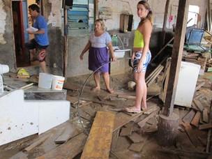 Lucia, no centro da foto, contabiliza o prejuízo com a destruição causada pela chuva (Foto: Tássia Thum/G1)