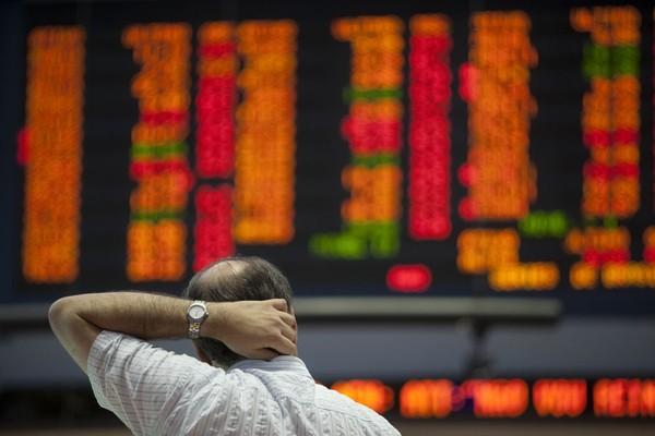 Homem observa índices em queda acentuada no painel da Bovespa, em São Paulo. O Brasil é um dos país com mais reservas da moeda americana no mundo, e seu mercado foi abalado pela revisão da nota da dívida dos EUA (Foto: AP)