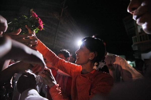 Aung San Suu Kyi recebe flores em Kawhmu na noite de sábado (31), véspera da votação (Foto: Soe Than Win/AFP)