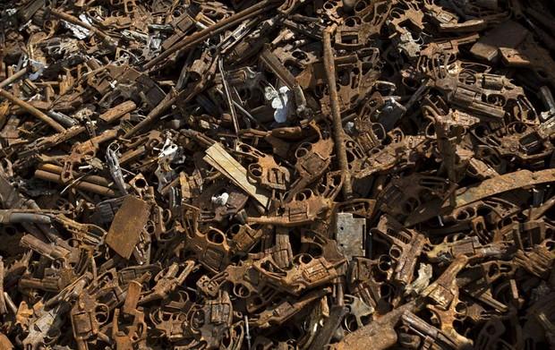 Milhares de pistolas sem as partes de madeira e plástico são vistas na caçamba de um caminhão em Volta Redonda (RJ) antes de serem destruídas, no primeiro dia da nova Campanha Nacional do Desarmamento. (Foto: Victor R. Caivano/AP)