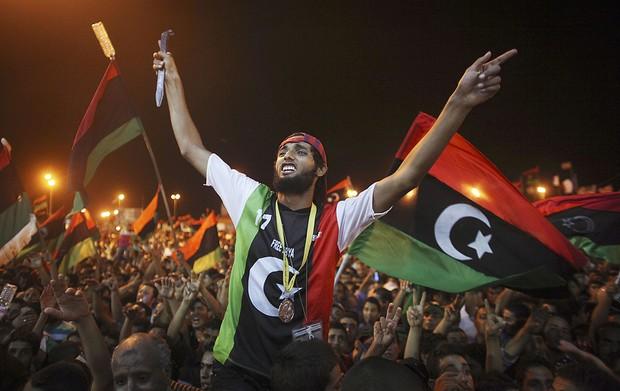 Com uma faca na mão, cidadão líbio comemorar prisão de um dos filhos de Kadhafi. (Foto: Alexandre Meneghini/AP)