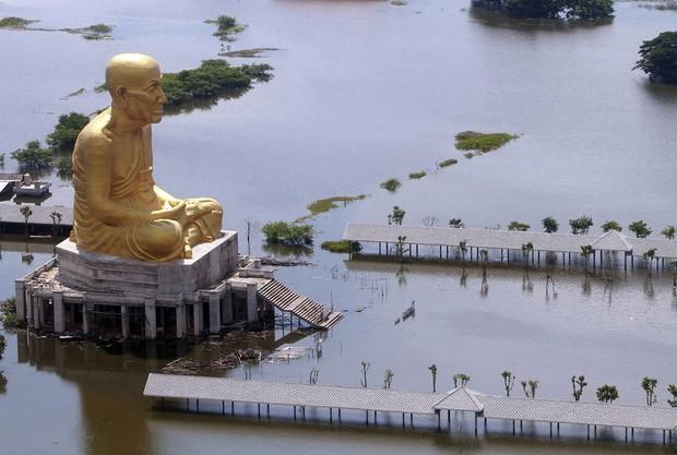 Estátua de Buda, localizada na província de Ayutthaya resiste durante forte enchente que atingiu a Tailândia (Foto: AP)