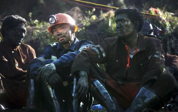 Oficiais de resgate descansam do lado de fora de uma mina de carvão no condado de Shizong, na província chinesa de Yunnan. Um vazamento de gás causou um desmoronamento que  provocou a morte de 21 pessoas e deixou mais de 20 mineiros presos na mina. (Foto: Reuters/China Daily)