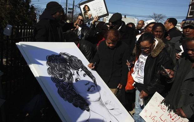 Fãs assinam cartaz com imagem de Whitney Houston nas proximidades da Igreja Batista New Hope (Foto: Shannon Stapleton/Reuters)