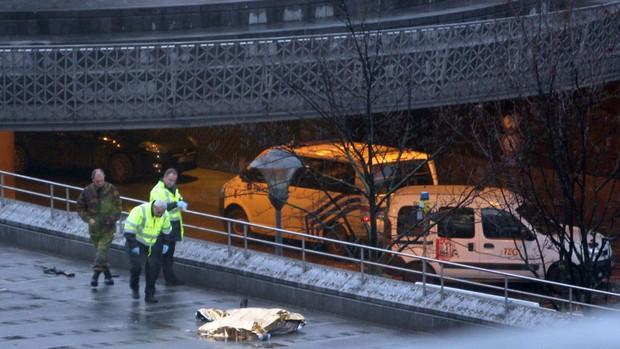 Oficiais observam corpo que seria do suposto atirador em Liége (Foto: AFP)
