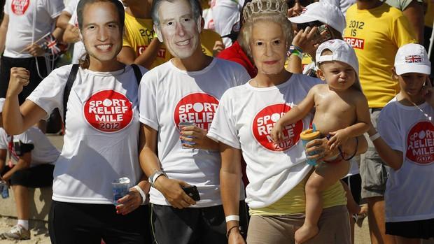 10/03 - Sábado - Fãs usam máscaras do Príncipe William, Príncipe Charles e Rainha Elizabeth em evento do Príncipe Harry no Rio (Foto: Reuters)