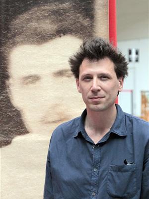 O livreiro francês Alban Causse posa em frente a uma reprodução do retrato inédito de Arthur Rimbaud descoberto em um mercado de pulgas.