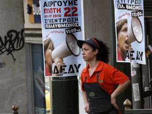 Trabalhadora em Atenas em frente a cartazes chamando para greve na Grécia