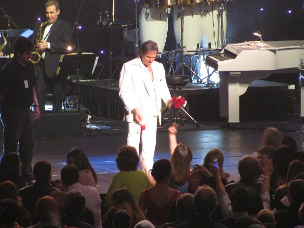 Roberto Carlos joga rosas para a plateia ao fim do show