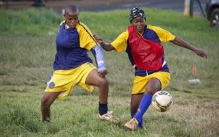 Jogadoras atuam em campo cheio de lama