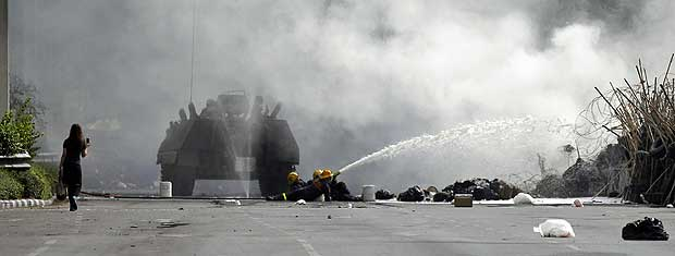 Blindado usa canhão de água para exterminar fogo em barricada e permitir que soldados do Exército avancem na direção de manifestantes antigovernistas.
