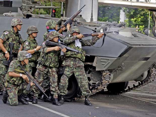 Soldados tailandeses disparam em Lumpini Park, no centro de Bangcoc, protegidos por um blindado.