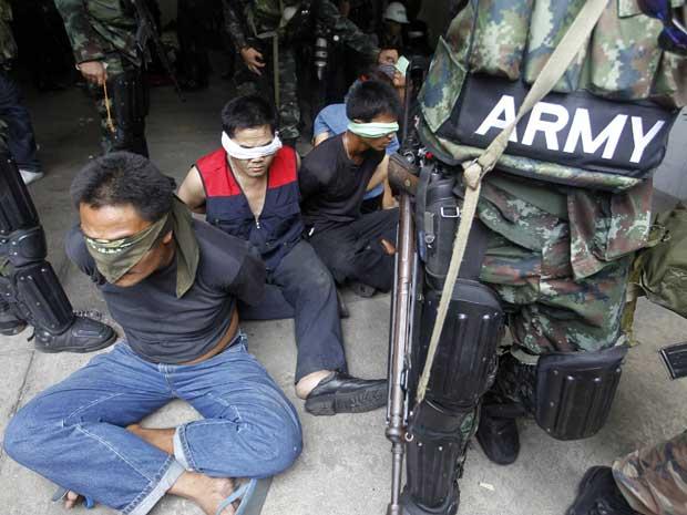 Integrantes de grupos ligados aos oposicionistas são vendados após serem presos em Bangcoc.