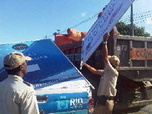 Agentes da Guarda Municipal ajudam a recolher placas irregulares.