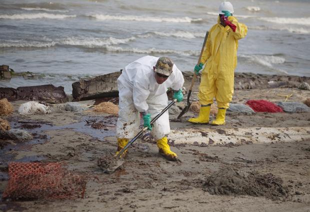 Trabalhadores contratados pela British Petroleum limpam praia no litoral da Louisiana, nos EUA.