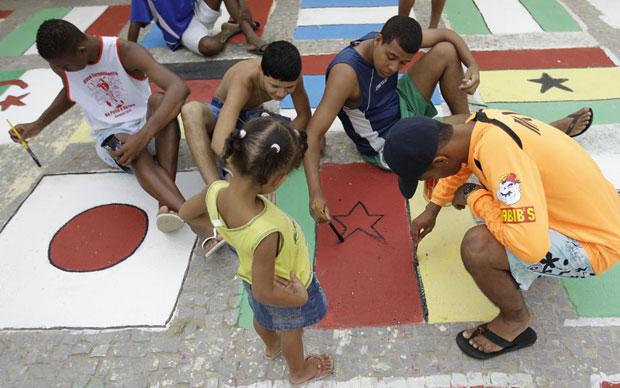 Crianças ajudam na decoração pintando bandeiras dos países que estarão na Copa