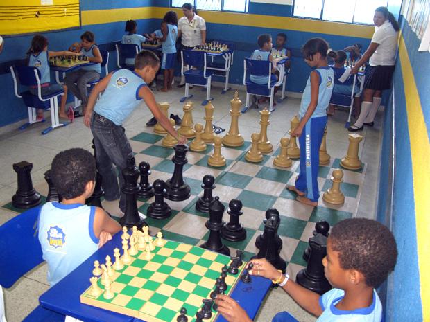 O tabuleiro estendido no chão e as peças gigantes transformam  o xadrez em uma brincadeira.