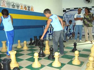 O coordenador do projeto e a secretária de Educação observam  com satisfação os alunos em uma disputa.