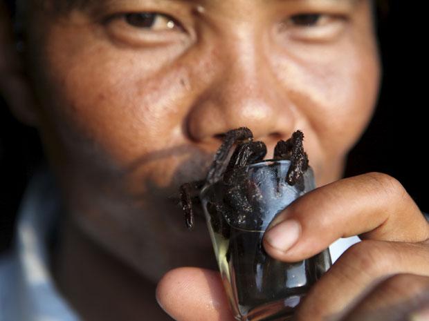 Homem bebe coquetel com tarântula no Camboja