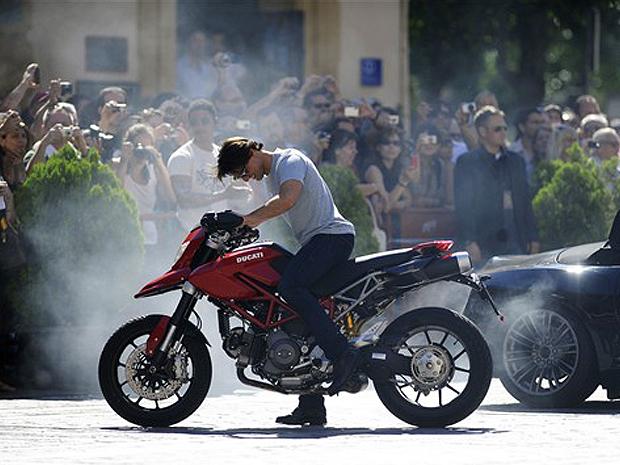 Tom Cruise acelera motocicleta em rua próxima à catedral de Sevilha.