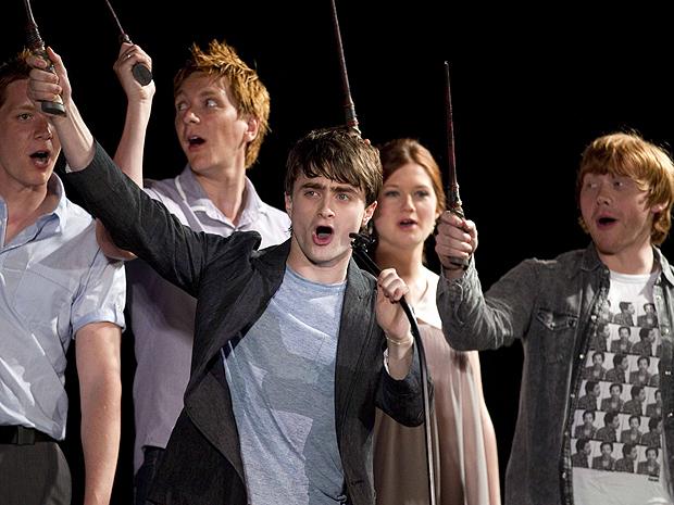 Daniel Radcliffe (à frente) e Rupert Grint ( à direita) sacodem varinhas mágicas nos EUA.