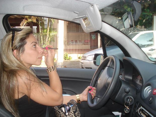 Motorista de maquia no espelho do carro