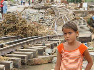 Menina olha cenário de destrição enquanto espera pelo pai em Branquinha