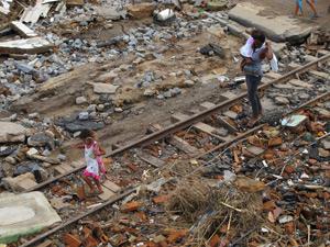Menina e a mãe caminham sobre trilhos suspensos em Murici