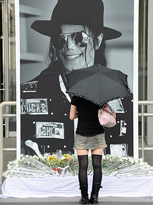 Fã observa pôster com imagem do rei do pop em Tóquio, no Japão