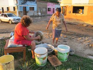 Mãe e filha tentam recuperar o que sobrou da casa e se  protegem contra saqueadores