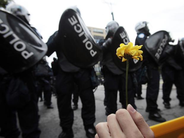 Manifestante segura uma flor na frente de barreira policial, em toronto, no Canadá