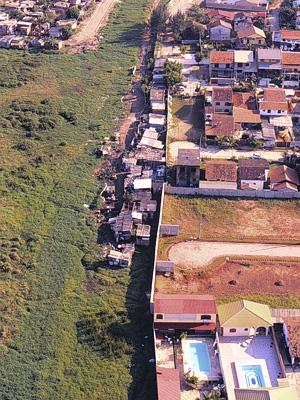 A foto, do ano 2000, mostra a ocupação irregular de Vargem  Pequena, tanto por barracos, como por casas luxuosas.