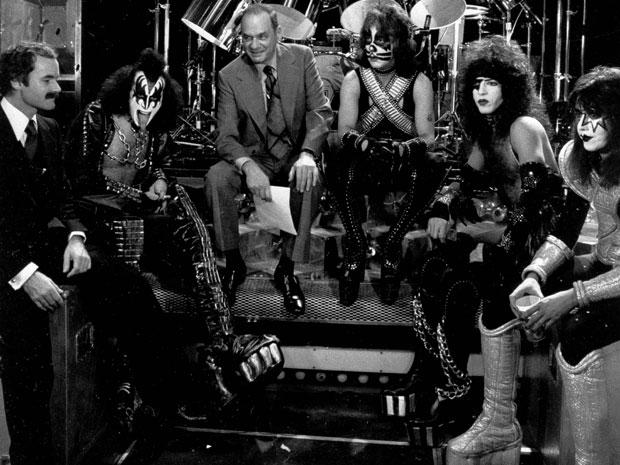 Bill Aucoin (à esquerda, de bigode) com os membros do Kiss e o apresentador de TV Edwin Newman, em 1977