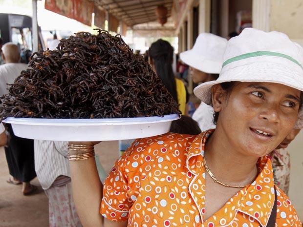 Mulher vende aranhas fritas em cidade do Camboja